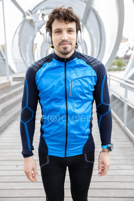 Bristled runner in workout clothes with headphones standing on bridge looking at camera — Stock Photo