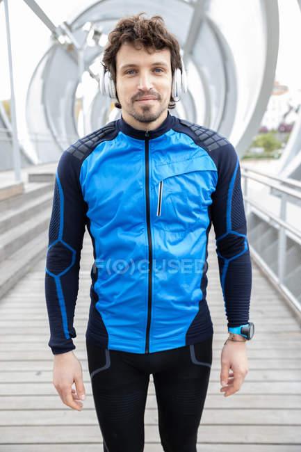 Borstiger Läufer in Trainingskleidung mit Kopfhörern, der auf einer Brücke steht und in die Kamera blickt — Stockfoto