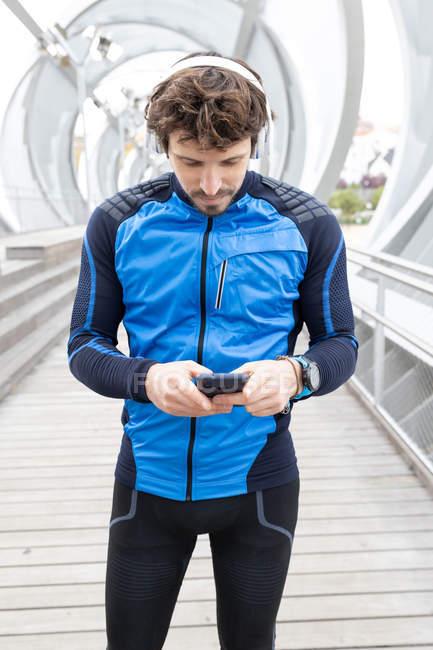 Corridore setolato in abiti da allenamento con cuffie in piedi sul ponte e messaggi di testo tramite smartphone — Foto stock