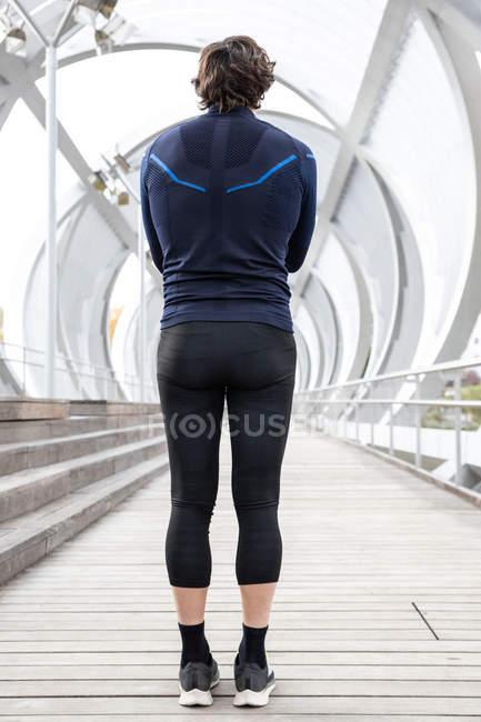 Передній погляд бігуна в тренувальному одязі, що стоїть на мосту. — стокове фото