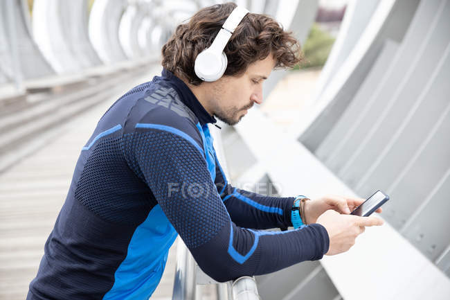 Side view of bristled runner in workout clothes with headphones leaning on fencing of boardwalk and text messaging via smartphone — Stock Photo