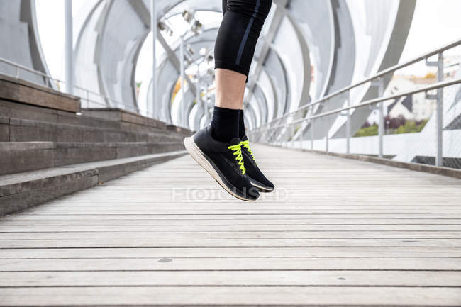 Cropped image of sportsman in workout clothing jumping while doing warm up exercises for training on boardwalk — Stock Photo