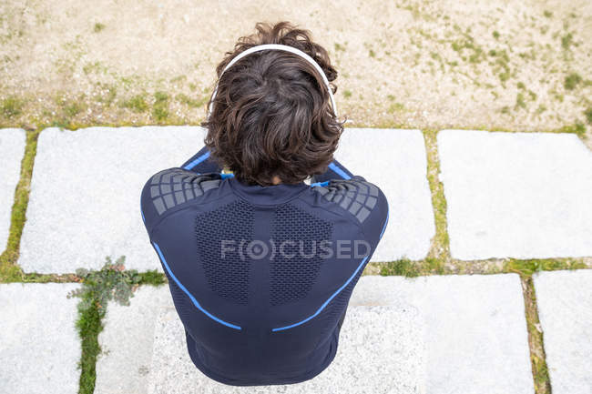From above back view of jogger in workout clothes sitting on cobbled ground while listening to music on headphones — Stock Photo
