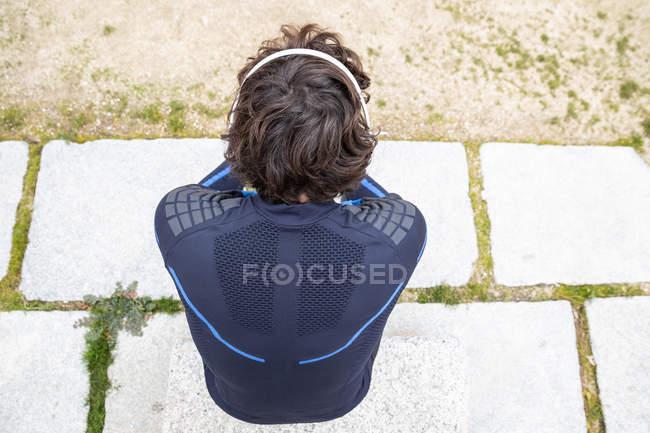 Зверху дивись, як бігун сидить на закрученій землі, слухаючи музику на навушниках. — стокове фото