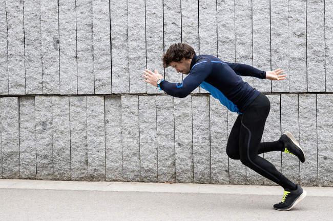 Vue latérale du joggeur masculin portant des vêtements d'entraînement bleus longeant un mur en béton et écoutant de la musique à travers un casque — Photo de stock