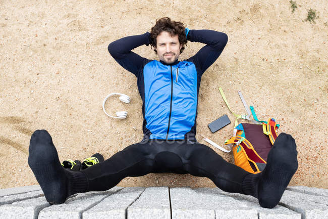 From above of sportsman in sportswear lying on sandy ground with phone and headphones near raising feet up on concrete wall — Stock Photo