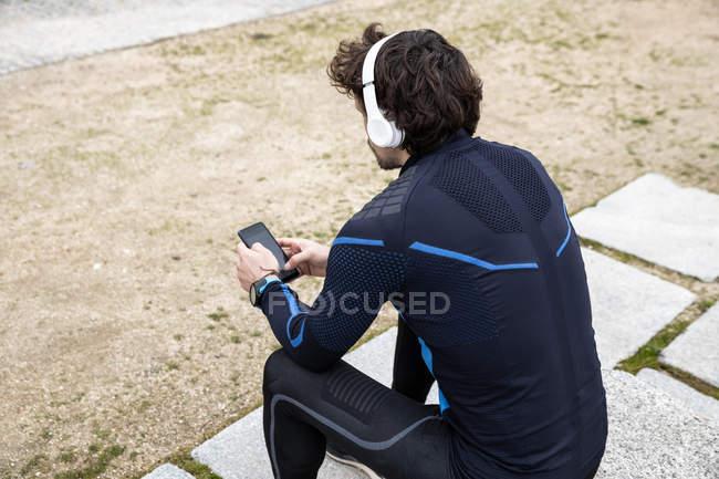Seitenansicht des lockigen, borstigen Joggers in Trainingskleidung, der auf Kopfsteinpflaster sitzt, während er per Smartphone SMS verschickt — Stockfoto