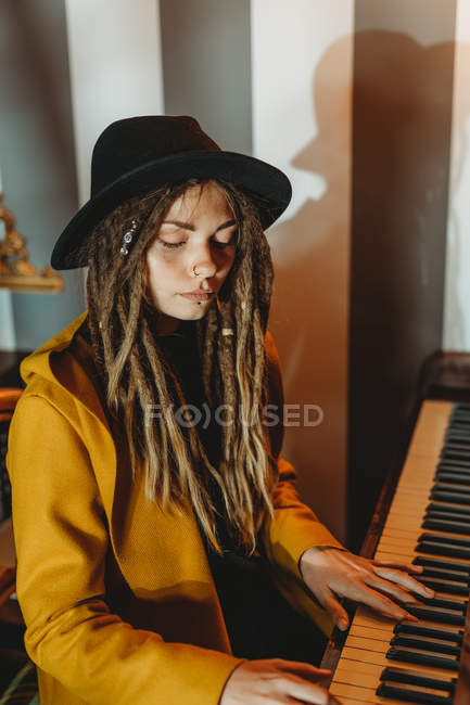 Side view of serious hipster female with dreadlocks wearing yellow coat and black hat playing piano while sitting in retro styled room — Stock Photo