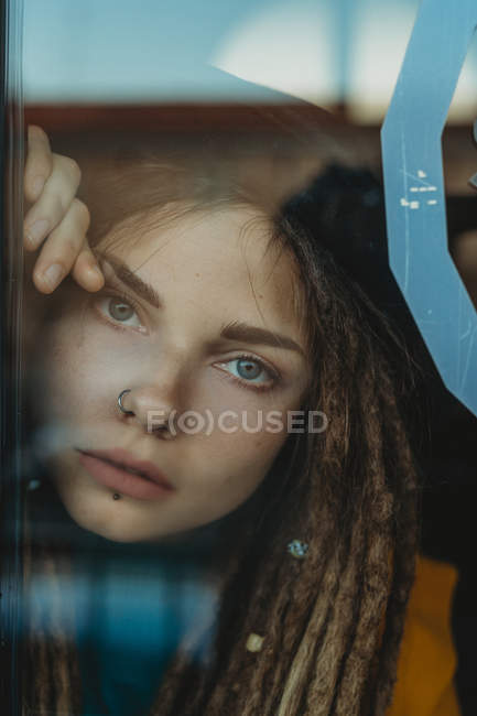 Pensive sad young female with dreadlocks leaning against window glass and looking away — Stock Photo