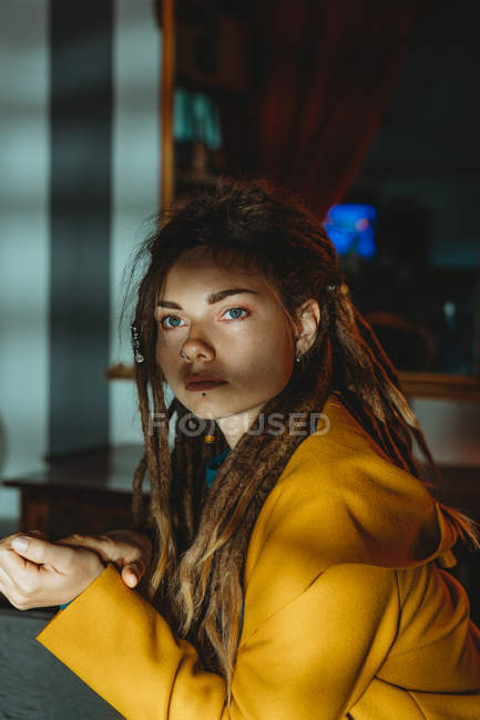 Stylish millennial female with dreadlocks wearing yellow coat over blue sweater looking away thoughtfully while sitting in room — Stock Photo