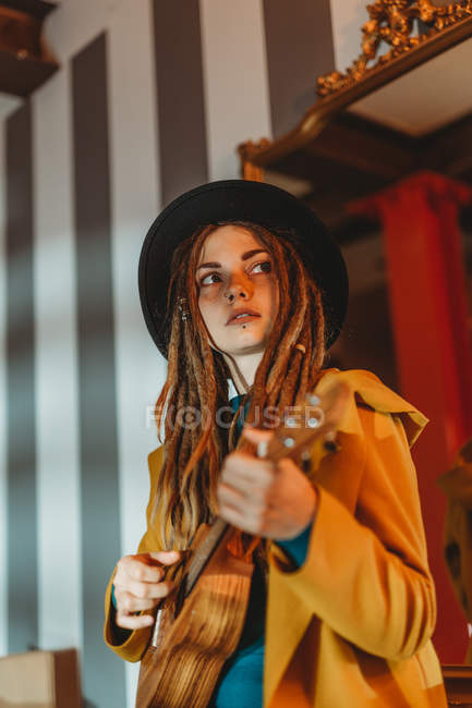 Young stylish woman with dreadlocks wearing yellow coat and black hat sitting on old wooden table back to mirror and playing Hawaiian guitar ukulele — Stock Photo
