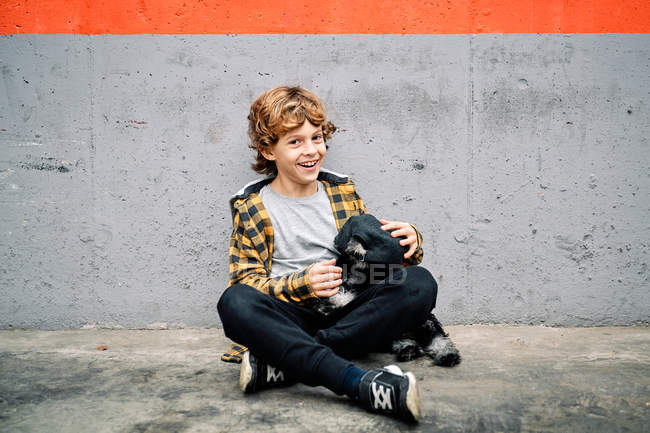 Happy boy in checkered shirt and cap sitting looking at camera next to concrete wall on street and holding Yorkshire Terrier puppy — Stock Photo