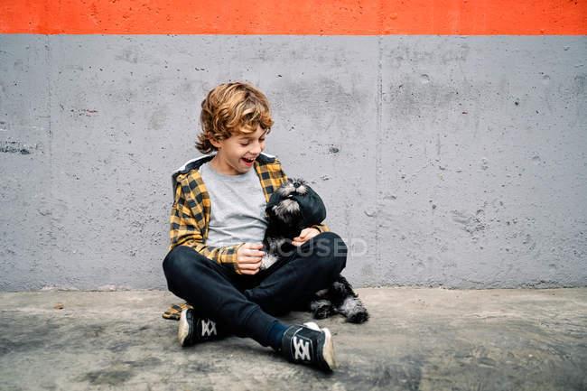 Joyeux garçon en chemise à carreaux et chapeau assis avec les yeux fermés à côté du mur de béton sur la rue et tenant Yorkshire Terrier chiot — Photo de stock