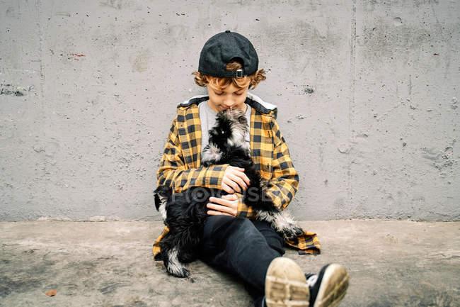 Triste ragazzo infelice in camicia a scacchi e cappello seduto con gli occhi chiusi accanto al muro di cemento sulla strada e tenendo Yorkshire Terrier cucciolo — Foto stock