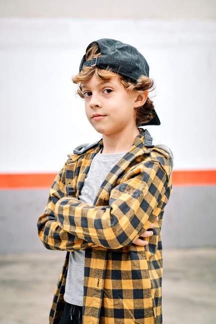 Позитивний стильний гіпстер хлопчик у чорно-жовтій сорочці з перевіркою, а чорний бейсбольний кепка стоїть зі схрещеними руками. — стокове фото