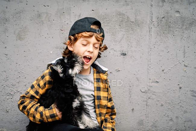 Счастливый мальчик в клетчатой рубашке и кепке сидит с закрытыми глазами рядом с бетонной стеной на улице и держит йоркширского терьера щенка — стоковое фото