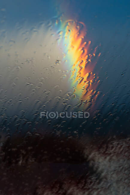 Raindrops on roof and rainbow in summertime — Stock Photo