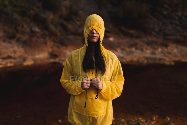 Mulher em capa de chuva amarela passeando na natureza — Fotografia de Stock
