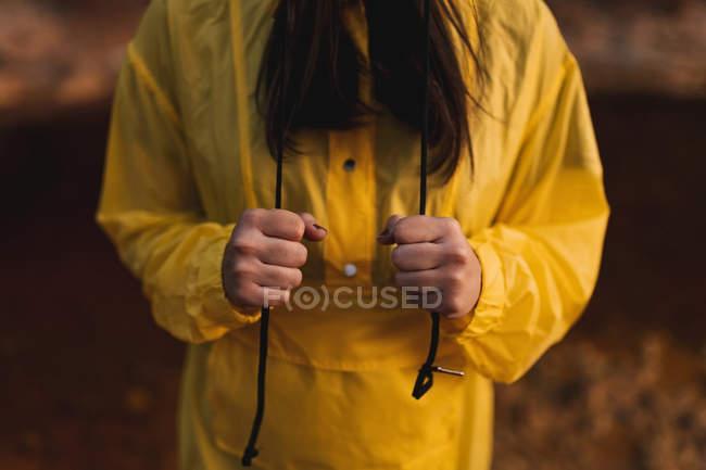 Жінка в жовтому плащі мандрує по природі — стокове фото