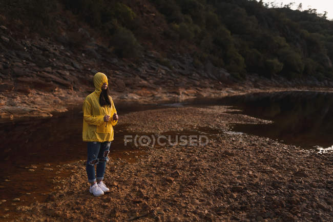 Woman in yellow raincoat strolling in nature — Stock Photo