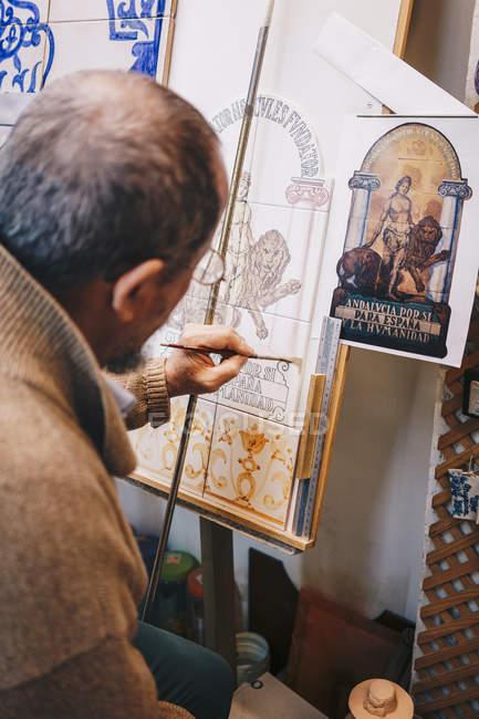 Сторона зору старшого майстра, який працює з керамічною плиткою на фарбі еа — стокове фото