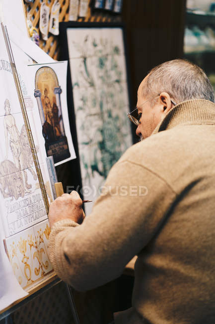 Side view of senior master working with ceramic tile on paint ea — Stock Photo