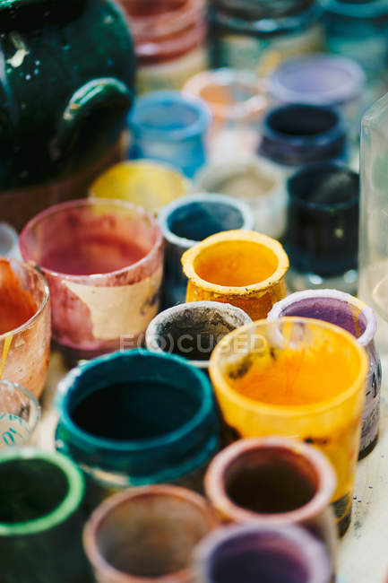 Glass cups with paints in workshop — Stock Photo