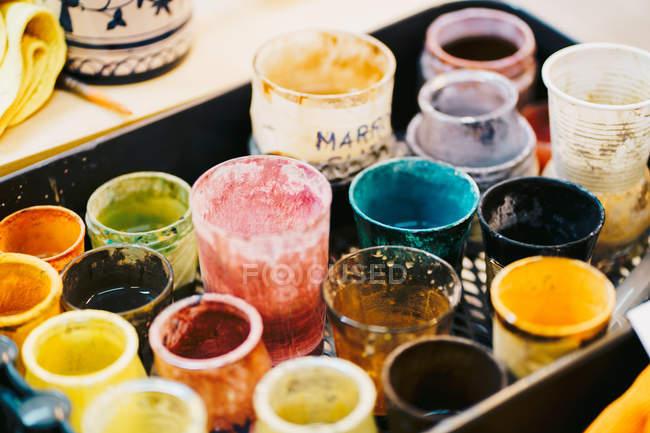 Tazze di vetro con vernici in officina — Foto stock
