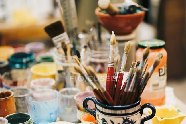 Pincéis em copo de cerâmica com padrão localizado na mesa entre — Fotografia de Stock
