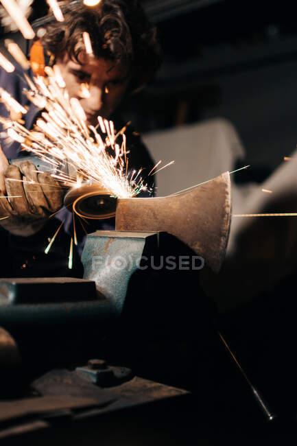 Роботодавець наточує сокиру електричним шліфувальником. — стокове фото