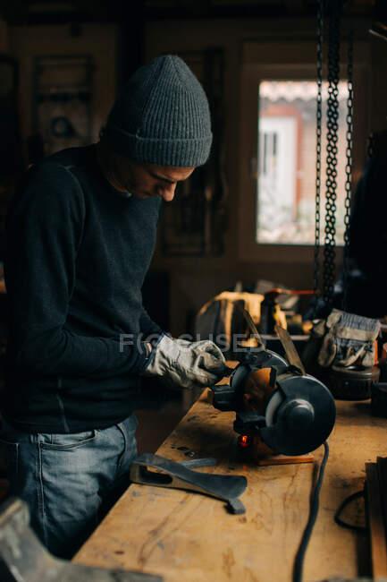 У майстерні ремісник перевіряє сокиру. — стокове фото