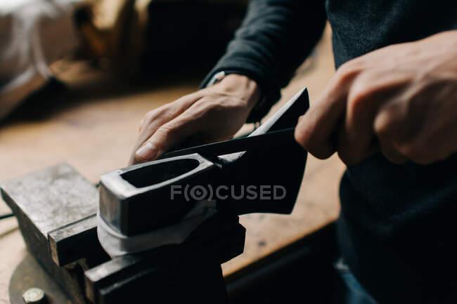 Erntehelfer überprüft Axt in Werkstatt — Stockfoto