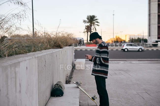 Side view of modern bearded man in grey cap and black t shirt and jeans using mobile phone while standing on skateboard — Stock Photo