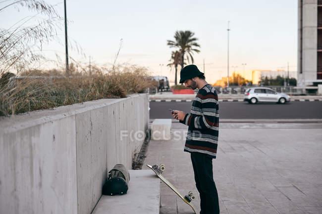 Бічний вид сучасної бородатої людини в сірій шапці і чорних футболках і джинсах за допомогою мобільного телефону, стоячи на скейтборді — стокове фото