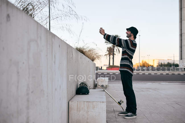 Side view of modern bearded man in grey cap and black t shirt and jeans taking a selfie picture on mobile phone — Stock Photo