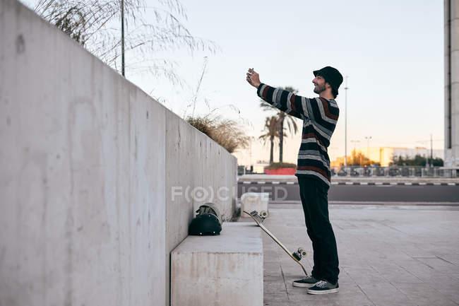 Бічний вид сучасного бородатого чоловіка в сірій шапці і чорна футболка і джинси роблять селфі фотографію на мобільному телефоні — стокове фото