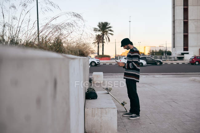 Side view of modern bearded man in grey cap and black t shirt and jeans using mobile phone while standing on skateboard in city — Stock Photo