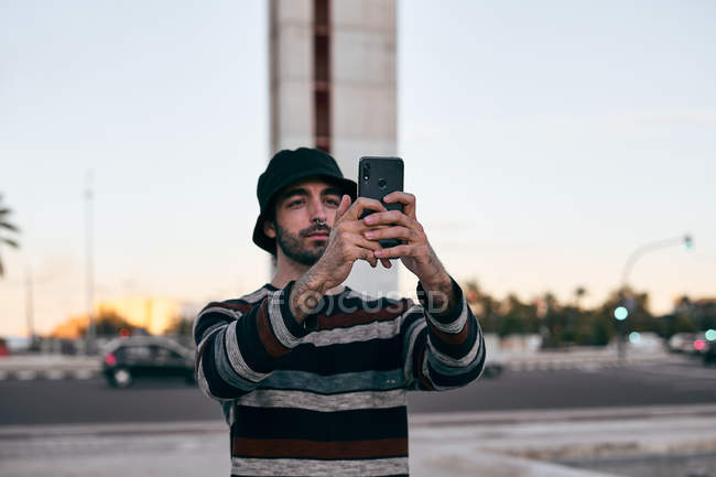 Modern bearded man in grey cap and black t shirt and jeans using mobile phone to take pictures while standing on skateboard in city — Stock Photo