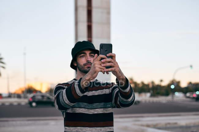 Сучасний бородатий чоловік у сірій шапці і чорні футболки і джинси, які використовують мобільний телефон, щоб робити фотографії, стоячи на скейтборді в місті. — стокове фото