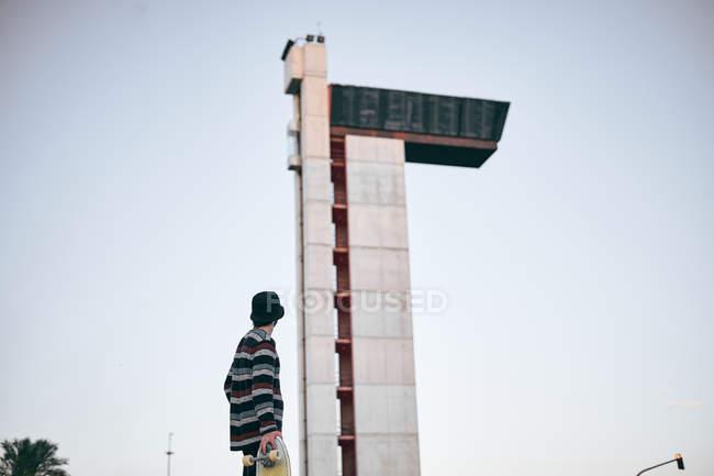 На задньому плані чоловік у капелюсі та смугастий светр з джинсами, що ходять з скейтбордом на вулицях міста. — стокове фото