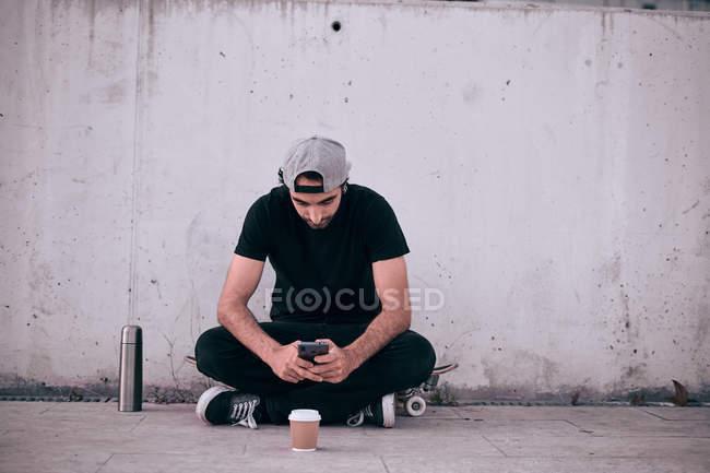Homem de barba jovem em boné cinza e t-shirt preta e jeans sentado no skate ao lado da parede de concreto usando telefone celular — Fotografia de Stock