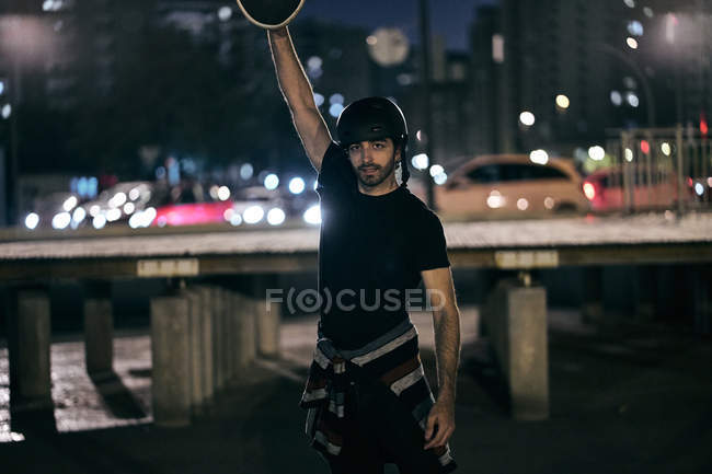 Cheerful bearded modern guy in black helmet and t shirt lifting up skateboard and looking at camera while enjoying summer evening in city — Stock Photo