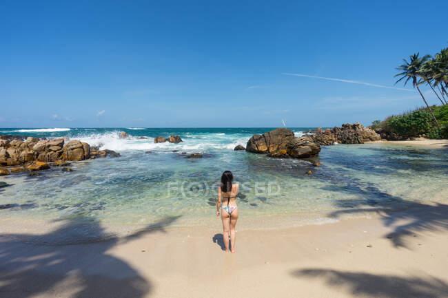 Signora in costume da bagno che riposa sulla spiaggia esotica solitaria — Foto stock