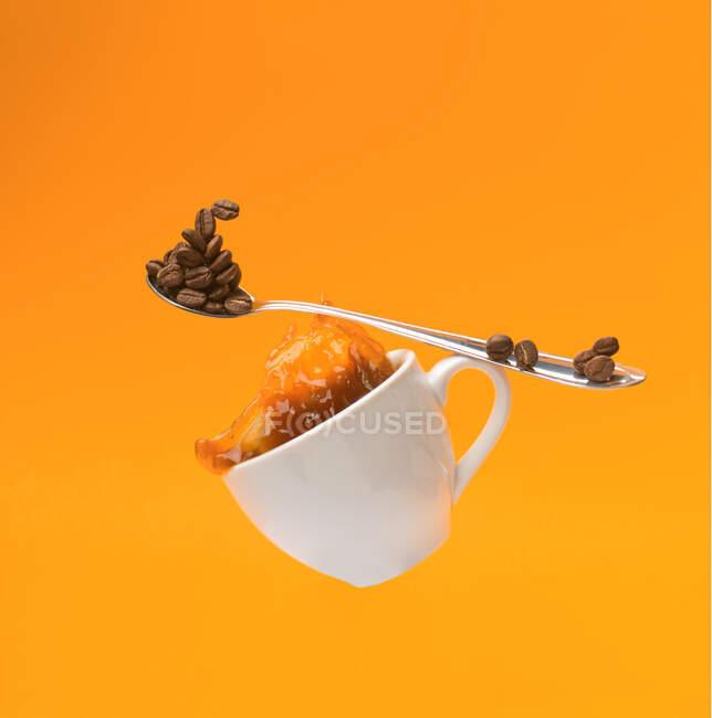 Weiße Tasse mit spritzendem Kaffee und Teelöffel — Stockfoto