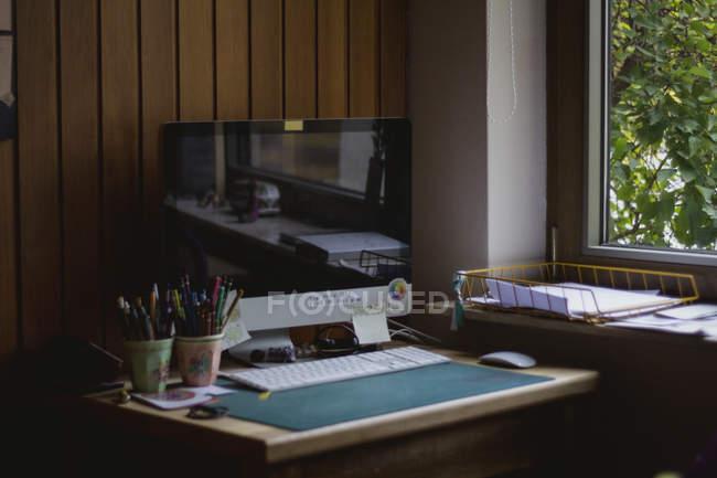Интерьер комфортабельного рабочего места с современным персональным компьютером рядом с окном дома в солнечный день — стоковое фото