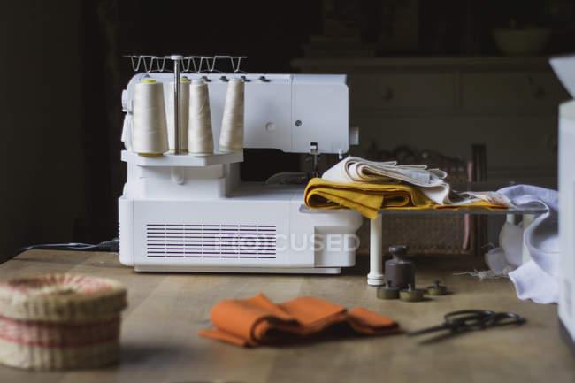 Posto di lavoro moderno di sarta con macchina da cucire e stoffa e fili su tavolo di legno a casa — Foto stock