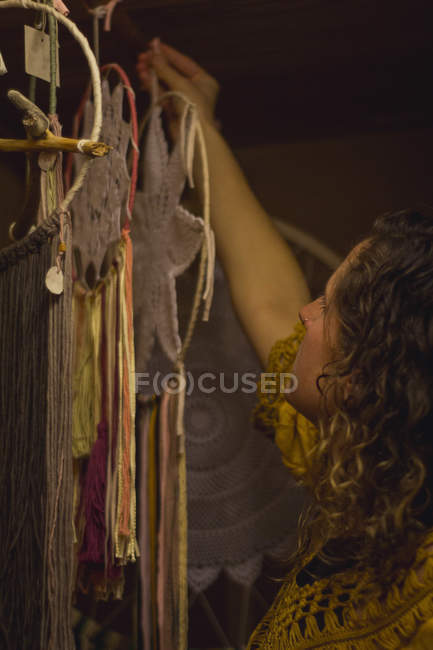 Side view of calm female taking handmade dreamcatcher with long threads looking at amulet spending time in house — Stock Photo