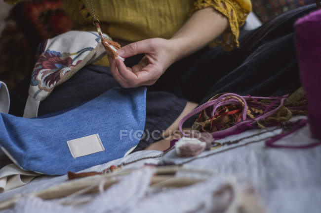 Cropped image of woman creating handmade dreamcatcher with long threads spending time in house — Stock Photo