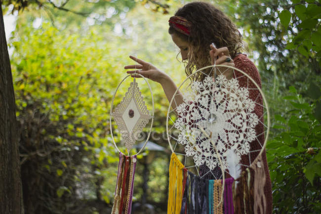 Woman in casual wear showing handmade dreamcatchers with long threads looking at amulet spending time in fresh air — Stock Photo
