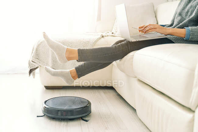 Side view of crop female in jeans and socks sitting on white sofa working on computer in room with laminate floor and putting feet on robotic vacuum cleaner — Stock Photo